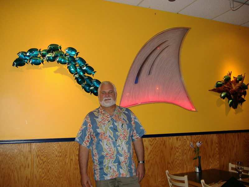 And a final picture with Eric, Fins' friendly and welcoming owner standing by the softly glowing Fin in the dining room wall. He traded in his ties for Aloha shirts. Mahalo, Eric!