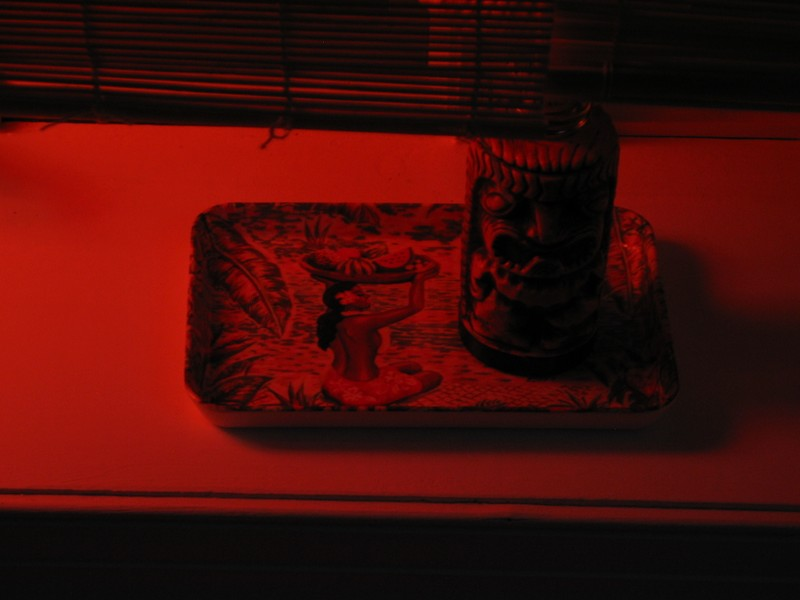 A Tiki table oil lamp sits on a small tray on one of the window sills. This is the real lighting in the Lounge...