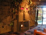 Inside the main lobby, the Tiki fireplace with another Tiki near the window. Through the window you can make out one of the many indoor pools. There are more small Tikis out there, but the camera would fog.