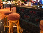 Blurry barstools, with the carpet faced underbar.