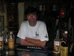 Unga Bunga, looking very happy behind his bar. The bar itself is a wonderful bamboo and thatch hut with two barstools.