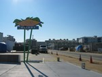 The Beach Colony's for sale sign is visible between the sign poles.