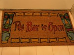 The nice new doormat my mom gave me for Yule! A very Tiki welcome! Indoors in winter and when the bar is closed, outside the bar door in nice weather when we're open.